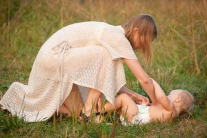 Mother changing babies cloth diaper