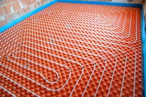 Installation of underfloor heating- orange panels and white plastic pipes.